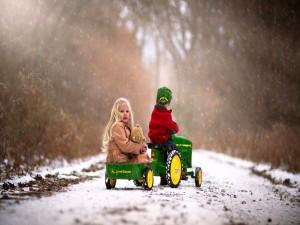 Niños jugando con un tractor bajo la nieve
