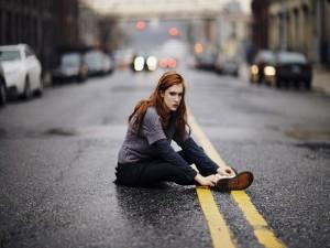 Chica enfadada sentada en una carretera