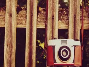 Cámara de fotos colgada de una valla de madera