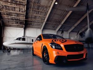 Mercedes Benz CLS 550 naranja en un hangar