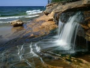 Agua cristalina cayendo al mar entre las rocas