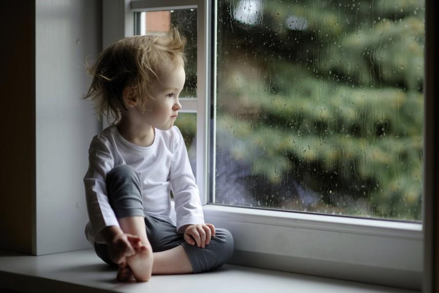 Una niña contemplando la lluvia por la ventana