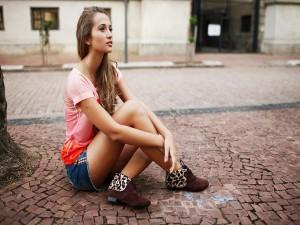 Chica sentada en el pavimento