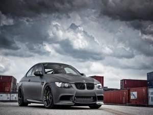 BMW gris junto a unos contenedores