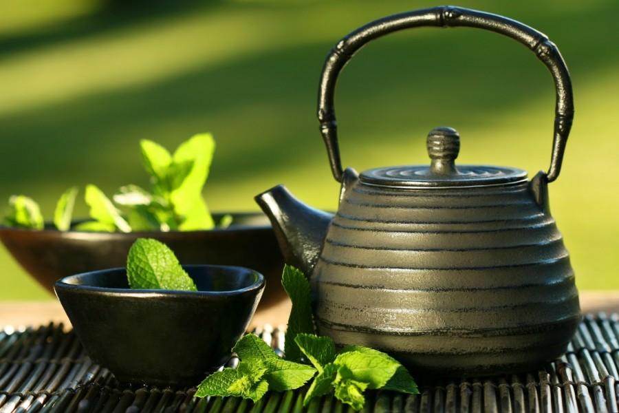Tetera negra asiática con hojas de té y menta