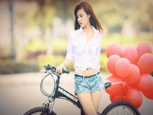 Chica transportando globos en una bici