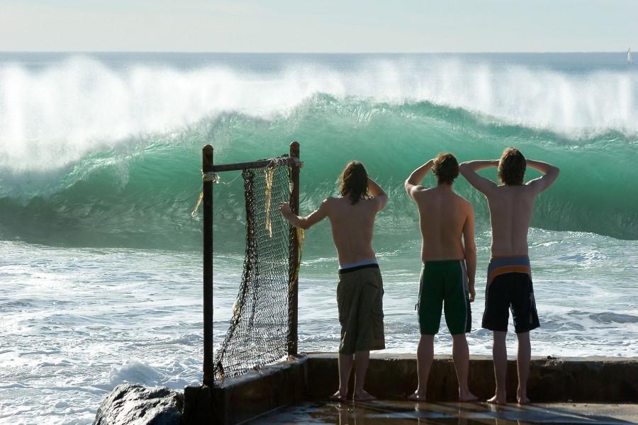 Tres chicos mirando las grandes olas