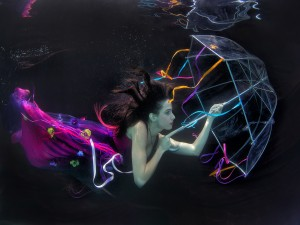 Mujer con un vestido y un paraguas bajo el agua