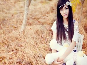 Chica asiática con un oso de peluche