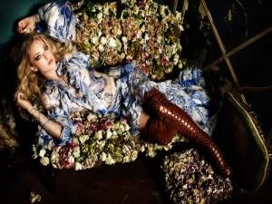 Amanda Seyfried tumbada sobre unas flores