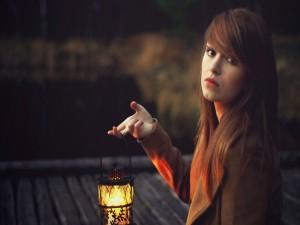 Chica sosteniendo un farolillo iluminado