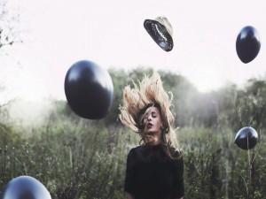 Globos negros en el aire junto a una mujer