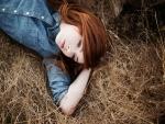 Chica tumbada sobre la hierba seca