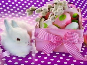 Blanco conejito junto a una cesta con huevos de Pascua