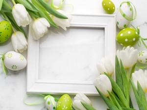 Tulipanes blancos y huevos de Pascua junto a un marco