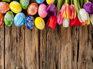 Huevos de Pascua y tulipanes sobre una madera