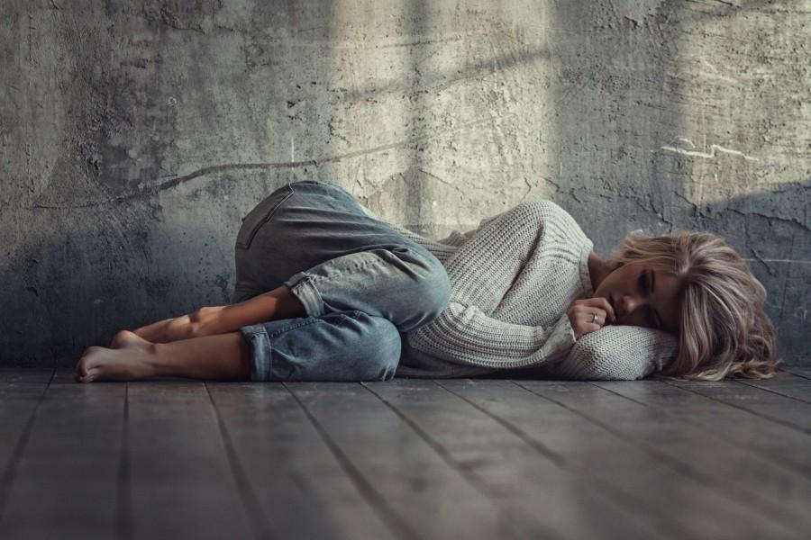 Mujer triste tumbada en el suelo