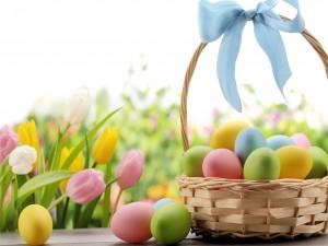 Cesta con moño y huevos de Pascua junto a unos bellos tulipanes