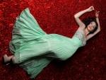 Modelo tumbada con un bonito vestido verde