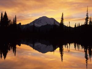 Montaña y amanecer reflejados en el lago
