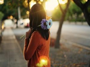 Chica sosteniendo dos flores