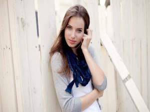 Una chica guapa junto a una valla