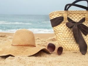 Canasto, sombrero y gafas sobre la arena