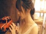 Chica observando un pequeño coche