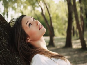Chica recostada sobre un tronco