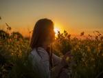 Mujer con un ramo de flores amarillas a la entrada del sol