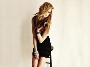 Avril Lavigne sentada en un taburete