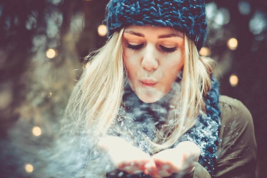 Chica soplando a la nieve