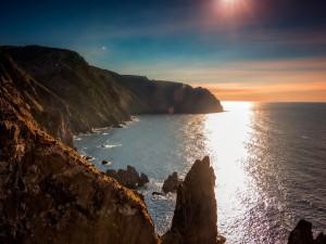 Resplandor del sol sobre el mar y las rocas
