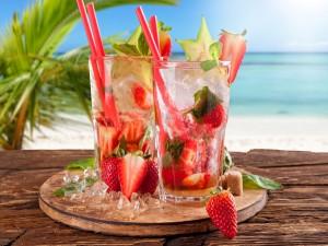 Refrescantes bebidas con fresas en una playa