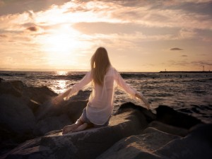 Chica contemplando el mar sobre unas piedras