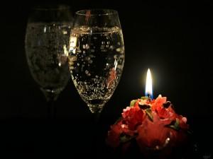 Una copa de champán junto a una vela