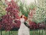 Mujer caminando a través de los árboles florecidos