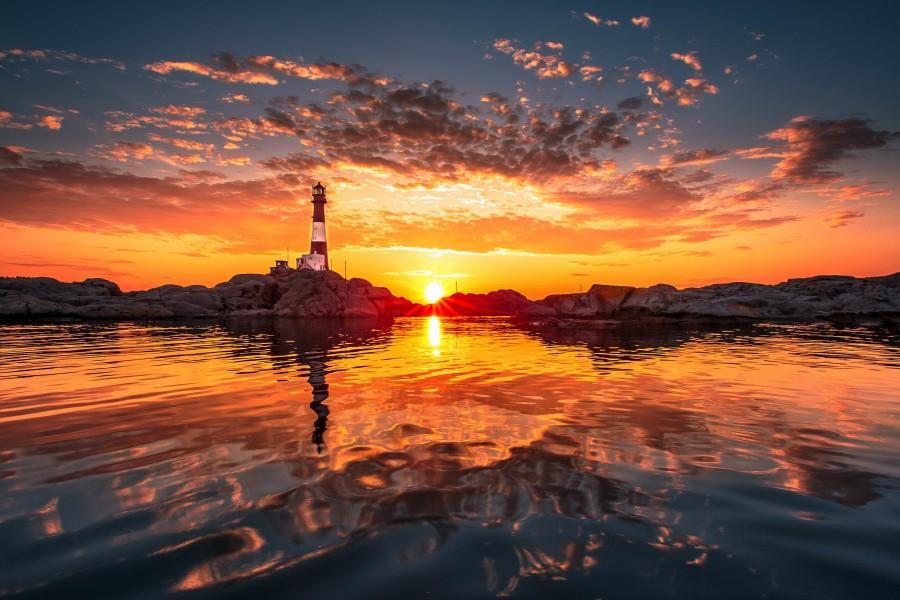 Faro reflejado en el agua en el ocaso del día