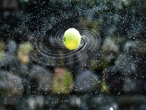 Una pelota de tenis mojada dando giros