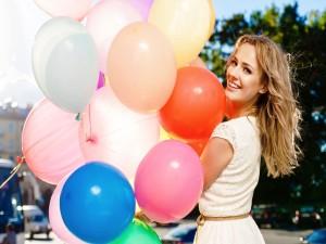 Mujer divirtiéndose con unos coloridos globos