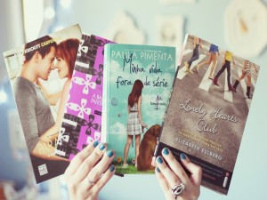 Chica con las uñas pintadas sosteniendo unos libros