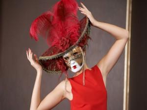 Mujer con máscara, sombrero y plumas de color rojo