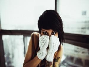 Chica cubriéndose la cara con unas manoplas blancas
