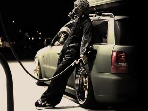 Hombres con máscaras de gas poniendo gasolina