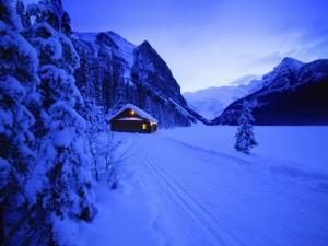 Cabaña iluminada en la nieve