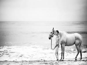 Chica paseando por la playa con el caballo