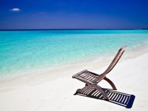 Silla de madera en la arena de la playa