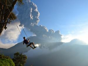 Hombre en un columpio con vistas al volcan en erupción