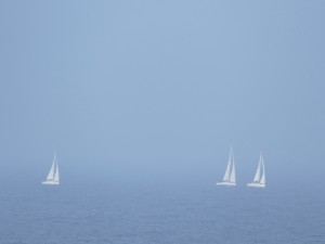Barcos de vela en el  mar en un día de niebla