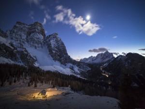 Cabaña iluminada al pie de la montaña